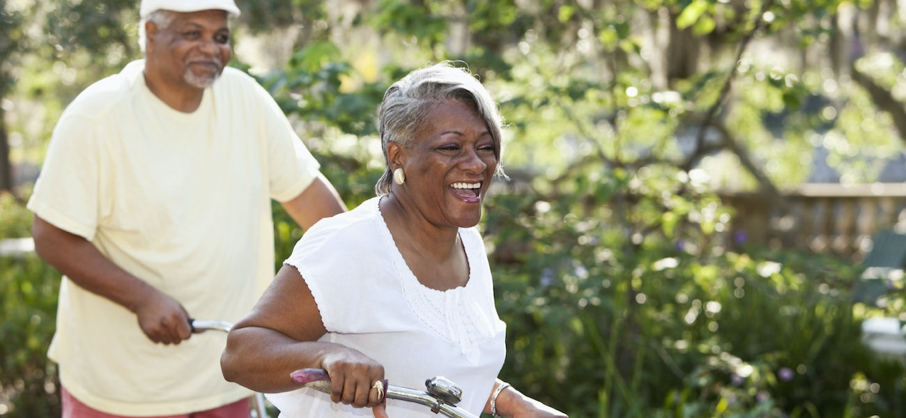 Homepage rotator with senior couple riding bikes together in a park